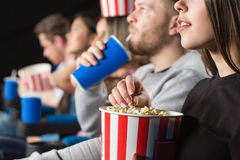Friends at the movies. Amazed viewers. Cropped closeup of a young women grabbing popcorn from a bucket while enjoying movies with her friends at the cinema Stock Image