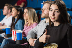 Friends at the movies. Best friends time. Beautiful brunette showing thumbs up while enjoying movies with her friends at the local movie theatre Royalty Free Stock Image