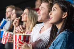 Friends at the movies. Chilling together. Shot of a cheerful group of friends watching movies eating popcorn at the local movie theatre Royalty Free Stock Photos