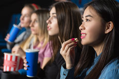Friends at the movies. Favorite leisure. Beautiful young asian women smiling cheerfully eating popcorn watching movies with her girlfriends Stock Image