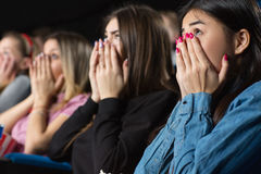 Friends at the movies. So into this movie. Group of female friends watching movies at the cinema looking scared covering their mouths with their hands Stock Images