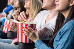 Friends at the movies. No movies without snacks. Cropped closeup of a cheerful men grabbing popcorn from his female friend at the movie theatre Royalty Free Stock Photo