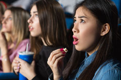 Friends at the movies. Oh come on! Beautiful asian women eating popcorn looking shocked watching movies with her female friends at the local cinema Stock Images