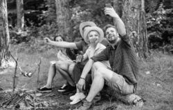 Friends near bonfire enjoy vacation and roasted food. Tourists sit log near bonfire taking selfie photo smartphone. Friends on vacation capture moment. Man stock photography