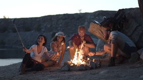 Friends near fireplace on the coast stock footage