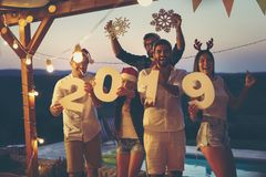 Friends at New Year`s Eve outdoor party by the pool royalty free stock photography