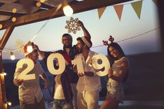 Friends at a New Year`s Eve party by the pool. Group of young friends having fun at a New Year`s Eve outdoor pool party, dancing and holding cardboard snowflakes royalty free stock photos