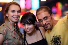 Friends night city. Three friends posing in night city. Shallow DOF Stock Photos