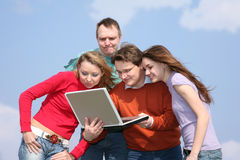 Friends with notebook. Group of people look on notebook Royalty Free Stock Photography