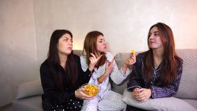 Friends offer bad food to girl on diet. Two friends urge woman to eat bad food. girl is on strict diet. concept of healthy intuitive nutrition, fast food debris stock video footage