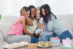 Friends offering gifts and hugging woman during party. Friends offering gifts and hugging women during party at home on couch Stock Image
