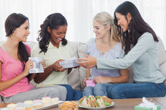 Friends offering gifts to dark woman during party. Friends offering gifts to dark women during party at home on couch Royalty Free Stock Photo