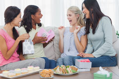Friends offering gifts to woman during party. Friends offering gifts to women during party at home on couch Stock Image