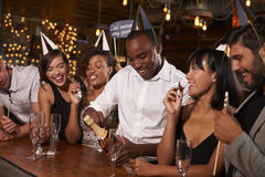 Friends opening champagne at a New Year�s party at a bar Royalty Free Stock Photography