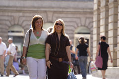 Friends out shopping. Friends walking down a busy shopping street on a sunny afternoon royalty free stock photo