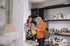 Friends Out Shopping. Two women are looking at products in a small shop together Royalty Free Stock Photos