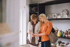Friends Out Shopping. Two women are looking at products in a small shop together Royalty Free Stock Photography