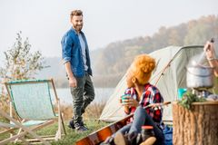 Friends during the outdoor recreation. Multi ethnic couple of friends dressed casually talking during the outdoor recreation with tent near the lake Stock Image