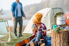 Friends during the outdoor recreation. Multi ethnic couple of friends dressed casually talking during the outdoor recreation with tent near the lake Royalty Free Stock Image