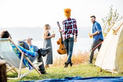 Friends during the outdoor recreation. Multi ethnic group of friends dressed casually having fun during the outdoor recreation at the camping near the lake Royalty Free Stock Photography