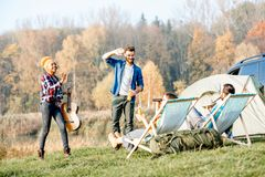Friends during the outdoor recreation. Multi ethnic group of friends dressed casually having fun during the outdoor recreation at the camping near the lake Royalty Free Stock Image