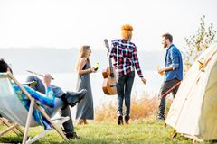 Friends during the outdoor recreation. Multi ethnic group of friends dressed casually having fun during the outdoor recreation at the camping near the lake Stock Image