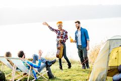 Friends during the outdoor recreation. Multi ethnic group of friends dressed casually having fun during the outdoor recreation at the camping near the lake Stock Photo