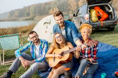 Friends during the outdoor recreation. Multi ethnic group of friends dressed casually having fun playing guitar during the outdoor recreation with tent, car and Royalty Free Stock Photos