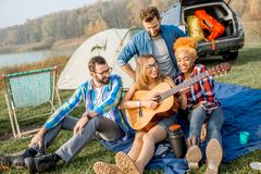 Friends during the outdoor recreation. Multi ethnic group of friends dressed casually having fun playing guitar during the outdoor recreation with tent, car and Stock Photo
