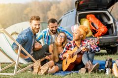 Friends during the outdoor recreation. Multi ethnic group of friends dressed casually having fun playing guitar during the outdoor recreation with tent near the Stock Image