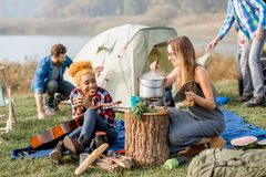Friends during the outdoor recreation. Multi ethnic group of friends dressed casually having a picnic, cooking soup with cauldron during the outdoor recreation Royalty Free Stock Photography