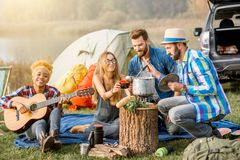 Friends during the outdoor recreation. Multi ethnic group of friends dressed casually having a picnic, cooking soup with cauldron, playing guitar during the Royalty Free Stock Images
