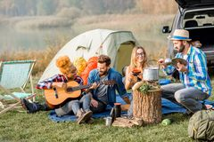 Friends during the outdoor recreation. Multi ethnic group of friends dressed casually having a picnic, cooking soup with cauldron, playing guitar during the Stock Photography
