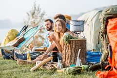Friends during the outdoor recreation. Multi ethnic group of friends dressed casually having a picnic, eating pizza, during the outdoor recreation with tent and Stock Photos