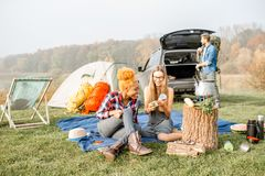 Friends during the outdoor recreation. Multi ethnic group of friends dressed casually having a picnic during the outdoor recreation with tent, car and hiking Royalty Free Stock Images