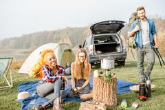 Friends during the outdoor recreation. Multi ethnic group of friends dressed casually having a picnic during the outdoor recreation with tent, car and hiking Stock Image