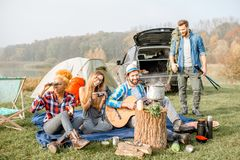 Friends during the outdoor recreation. Multi ethnic group of friends dressed casually having a picnic during the outdoor recreation with tent, car and hiking Royalty Free Stock Image
