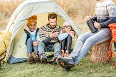 Friends during the outdoor recreation. Multi ethnic group of friends dressed in sweaters warming up together sitting in the tent during the outdoor recreation Royalty Free Stock Photo