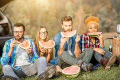 Friends during the outdoor recreation. Multi ethnic group of friends having a picnic, eating watermelon during the outdoor recreation Royalty Free Stock Photo