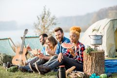 Friends during the outdoor recreation. Multi ethnic group of friends having a picnic, eating watermelon during the outdoor recreation with tent, car and hiking Royalty Free Stock Photos