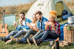 Friends during the outdoor recreation. Multi ethnic group of friends having a picnic, eating watermelon during the outdoor recreation with tent, car and hiking Stock Photo