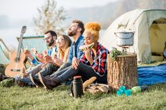 Friends during the outdoor recreation. Multi ethnic group of friends having a picnic, eating watermelon during the outdoor recreation with tent, car and hiking Stock Photography