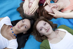 Friends outdoors with heads together Royalty Free Stock Photos