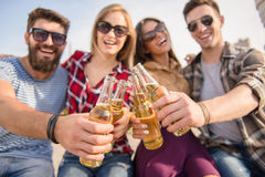 Friends outdoors. Young happy people walking outdoors. Drinking beverages Royalty Free Stock Photos