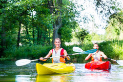 Friends paddling with canoe on forest river Royalty Free Stock Photography