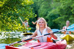 Friends paddling with kayak or canoe on forest river. Women and men with kayak or canoe on forest river stock photography