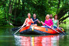 Friends paddling on rubber boat at forest river or creek Royalty Free Stock Image
