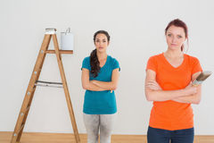 Friends with paint brushes and ladder in a new house Royalty Free Stock Image