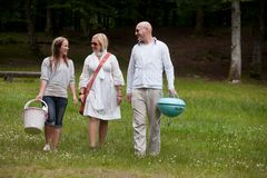 Friends in Park Ready for BBQ. Friends walking in park ready for a BBQ picnic royalty free stock image