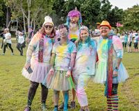 Friends Participating In Color Frenzy Fun Run. MACKAY, QUEENSLAND, AUSTRALIA - JUNE 2019: Unidentified people splashed with colored powder posing before a Color stock images